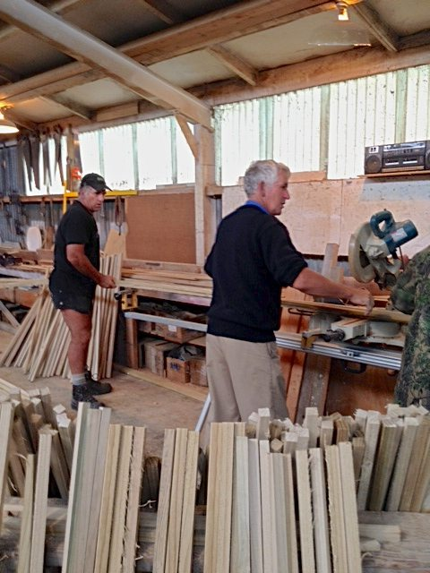 """Mike Whale, left, guides the lengths of wood being cut to the correct size by Alan Taylor, using a radial arm saw in preparation for use as wordless walking sticks at the Southern Field Days. Six meter 2x2's were first split length wise on a table saw and then split again to get the desired 1"""" x 1"""" x 1m walking stick. Mike Whjale and Alan Taylor are both team members of the Lower Mataura Valley Ministers Group that invited FCFI to come to Southland. Over 400 walking sticks were sanded and rawhide bracelets attached for the Southern Field Days."""